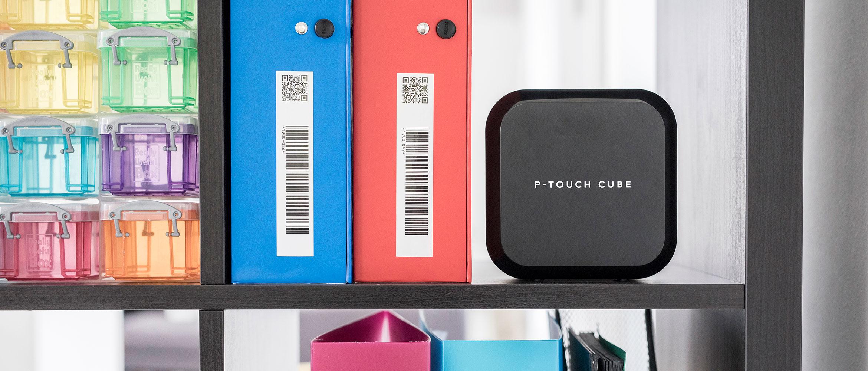 Принтер для наклеек Brother P-touch на полке рядом с промаркированными папками со штрих-кодами