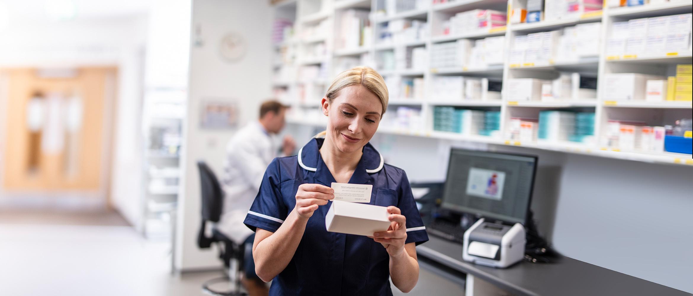 healthcare worker labelling a bottle of medicine
