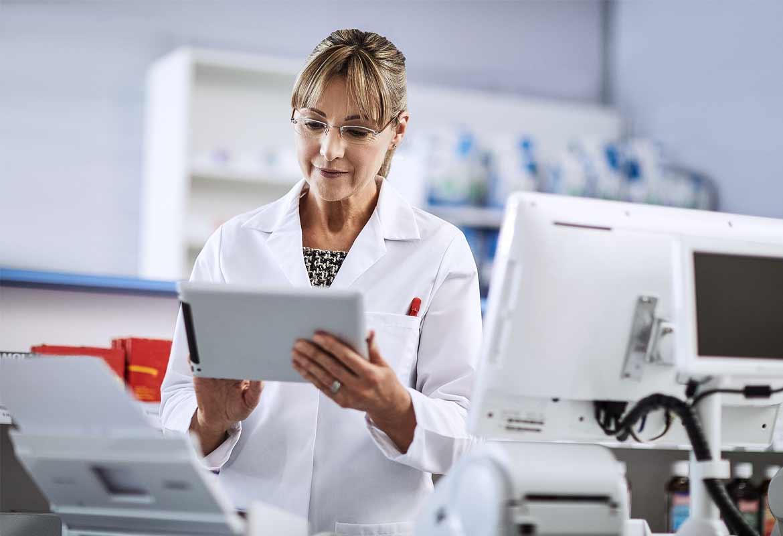 Female pharmacist wearing white coat using tablet device