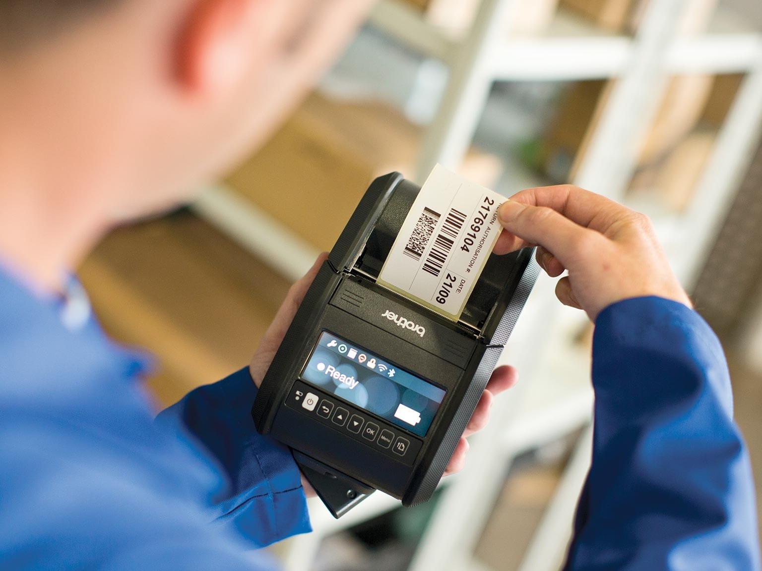 Рабочий склада с принтером RJ в ожидании печати наклейки
